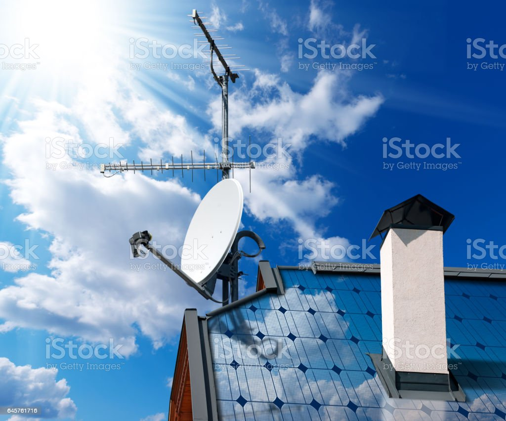 House Roof with Solar Panels and Antennas stock photo