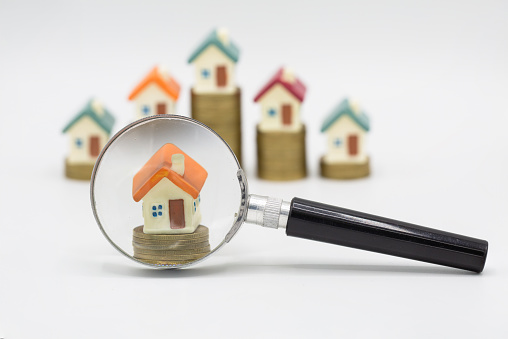 istock House searching concept with a magnifying glass on white background. Stack coin and bar graph with grow,   magnifying glass searching for a new home, Loan for real estate. 1173021605
