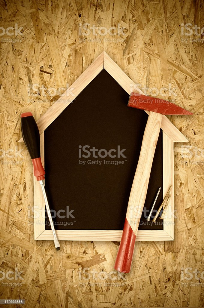 House shape blackboard and work tools royalty-free stock photo