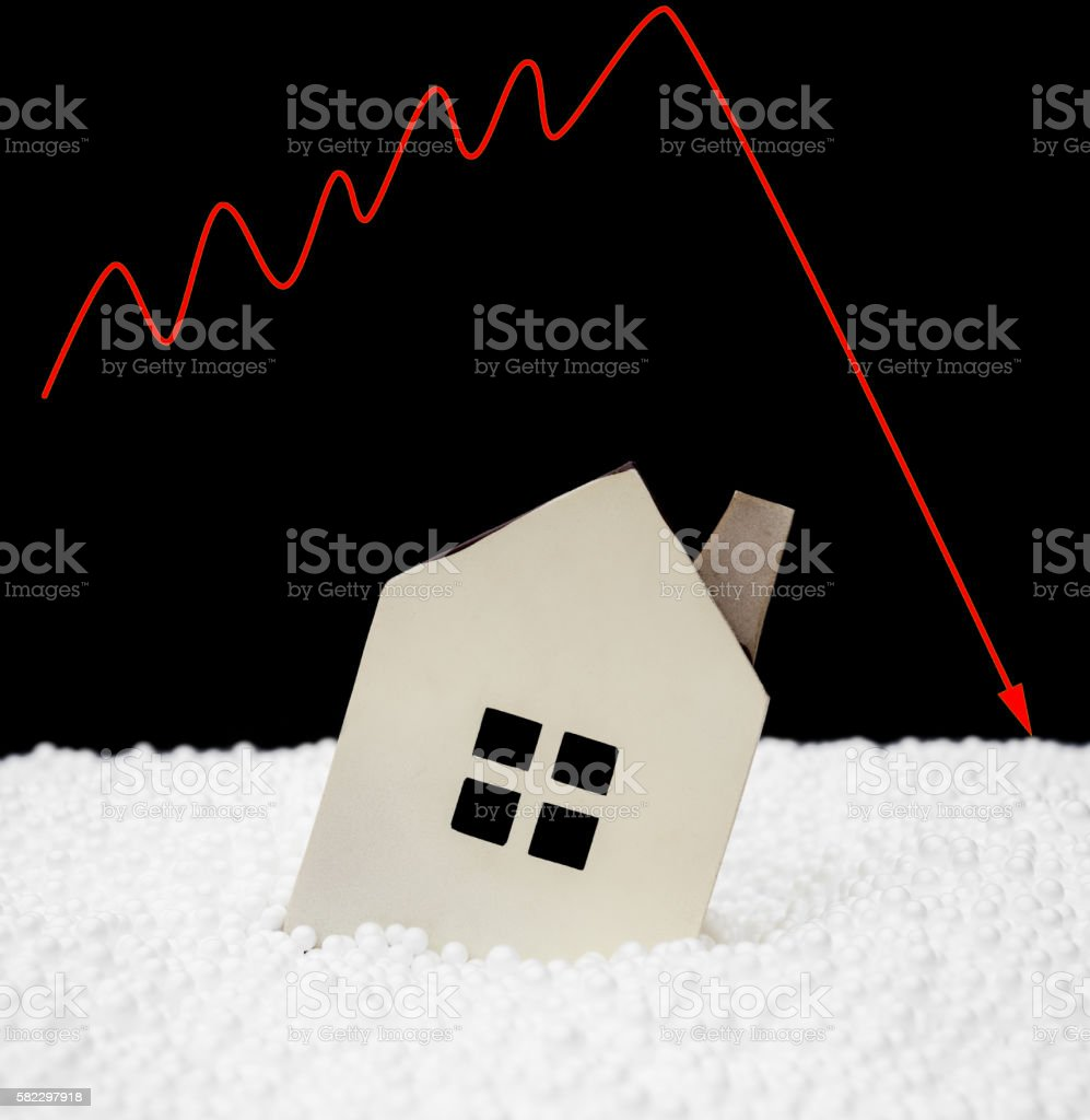 house sinking into polystyrene particle with a downward arrow stock photo