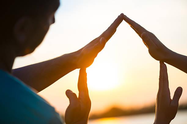 haus-symbol mit den händen gegen sonnenuntergang - dachformen stock-fotos und bilder