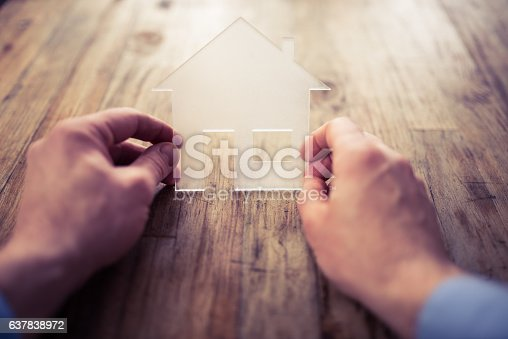 istock house symbol with hands against  sunset 637838972
