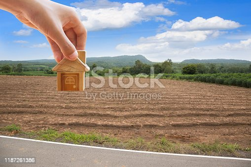 istock House symbol with location pin and Empty dry cracked swamp reclamation soil, land plot for housing construction project with and beautiful blue sky with fresh air Land for sales landscape concept 1187261386