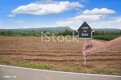 istock House symbol with location pin and Empty dry cracked swamp reclamation soil, 1188641765