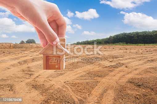 istock House symbol with location pin and Empty dry cracked swamp reclamation soil, 1215675436