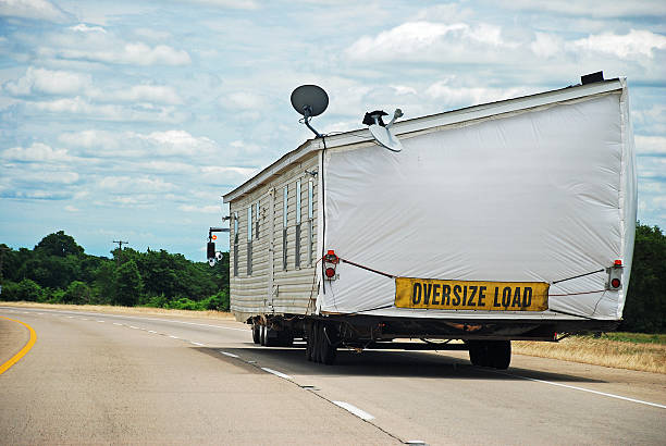 House Trailer on Interstate Highway Half of double-wide house trailer being transported along interstate highway. manufactured housing stock pictures, royalty-free photos & images
