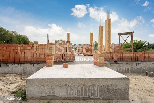 House under construction. New residential building with support element and brick wall on foundation