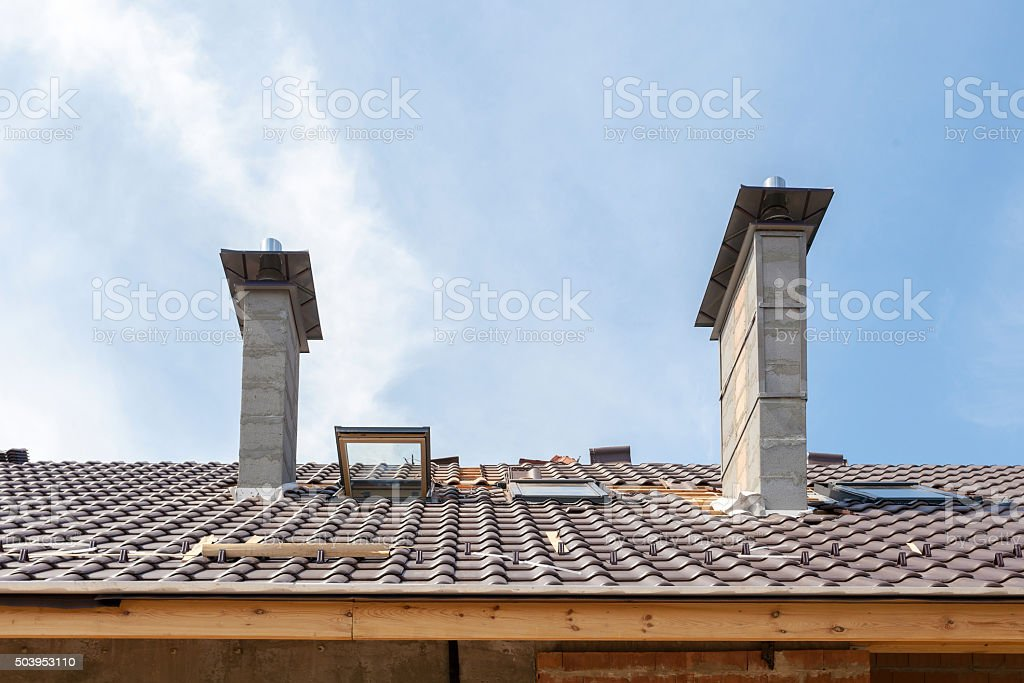 House under construction. Roofing tiles installation. New roof with skylight stock photo