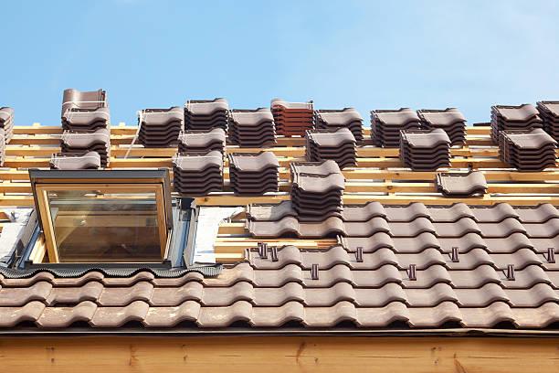 haus im bau. roofing fliesen und oberlicht geöffnet - schiefer fliesen stock-fotos und bilder