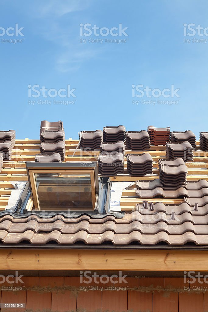 House under construction. Roofing tiles with open skylight stock photo
