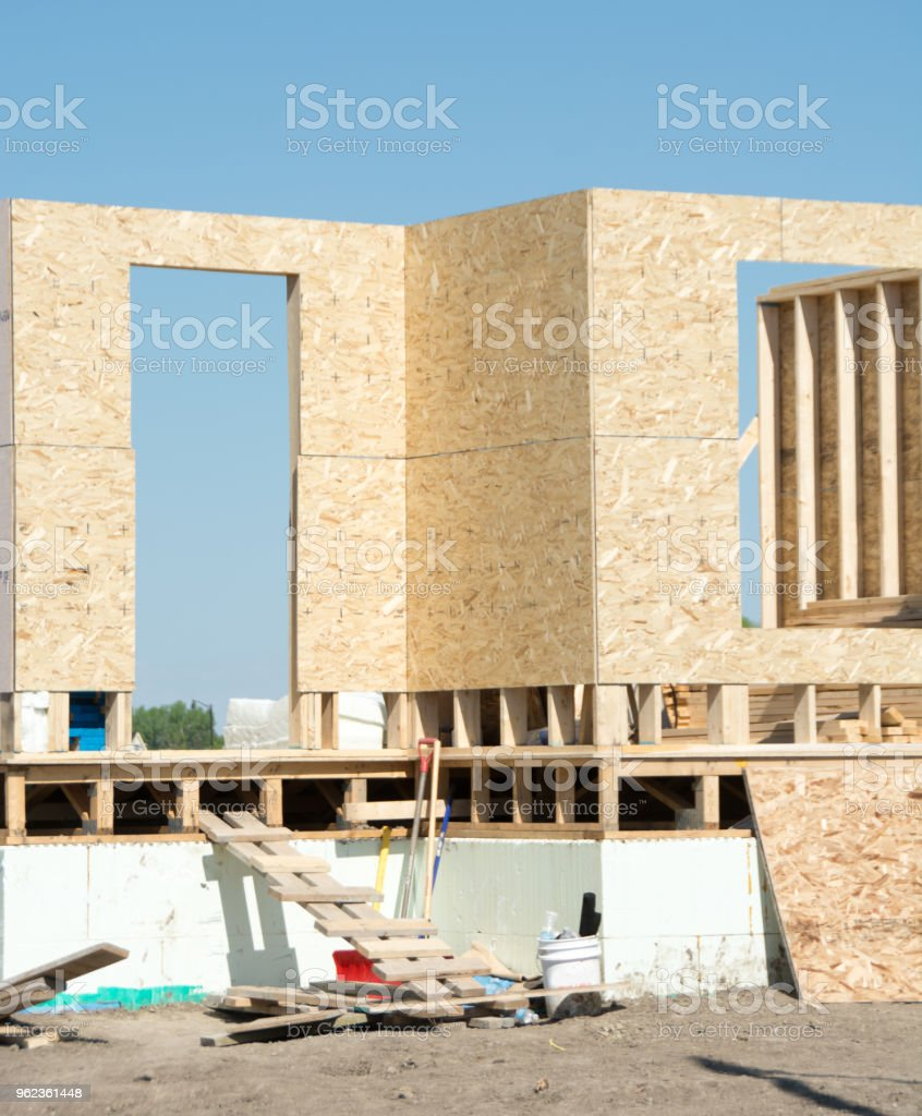 House under recently started construction with framing stock photo
