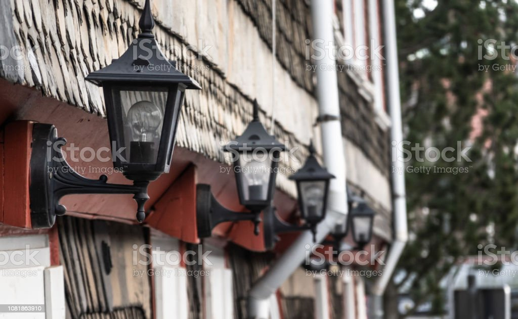 House wall in the old town with forged black iron lamps arranged in a...