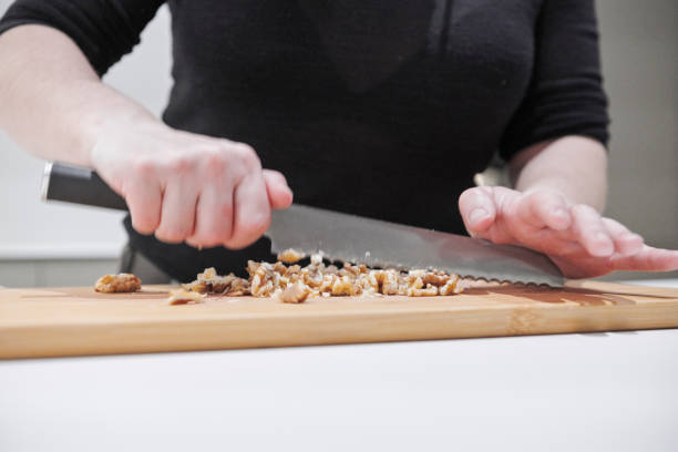 House wife cutting walnuts on wooden board stock photo