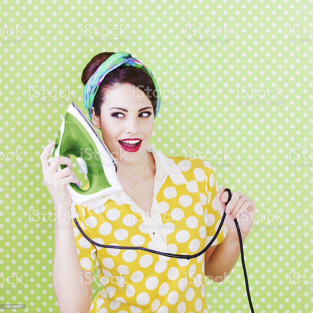 House wife using an iron as a phone, humor. stock photo