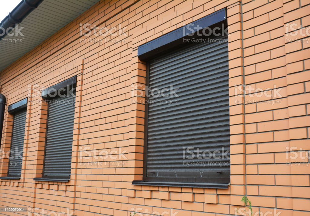 House Windows with rolling shutters for home protection. stock photo