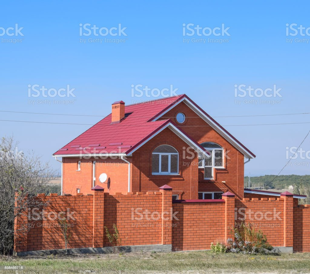 house with a red roof and red brick. Red brick fence. Roof of metal. stock photo