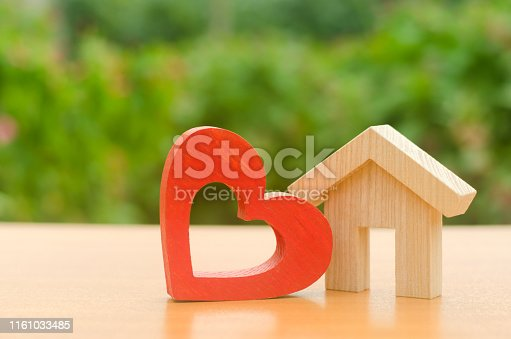 istock House with a red wooden heart. House of lovers. Affordable housing for young families, support program. Parental hospitable home. Housing construction of your dreams. Buying and renting real estate. 1161033485