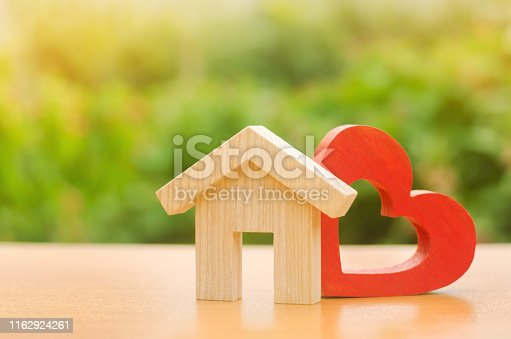 istock House with a red wooden heart. House of lovers. Parental hospitable home. Housing construction of your dreams. Buying and renting real estate. Affordable housing for young families, support program. 1162924261