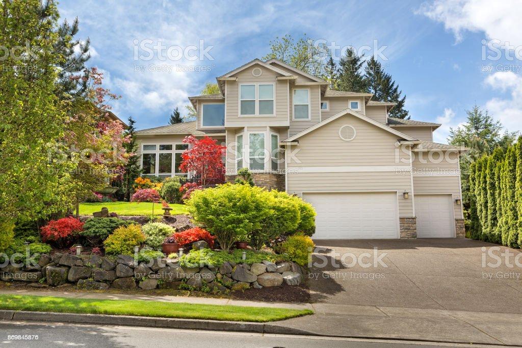 House with green lawn manicured frontyard garden in suburban residential neighborhood USA stock photo