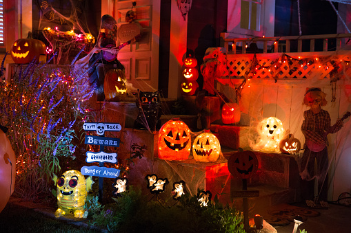 A house with Halloween pumpkins and halloween decorations at  Halloween night on a city street. Trick or treat.