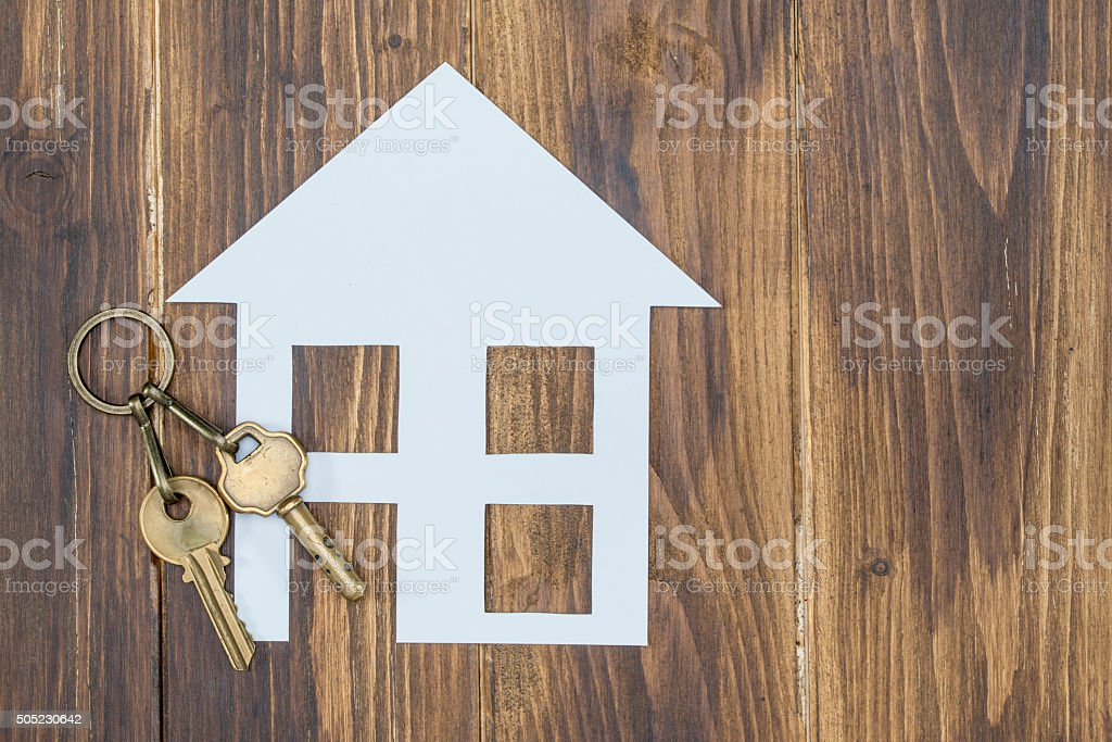 house with key on wooden background, new house stock photo