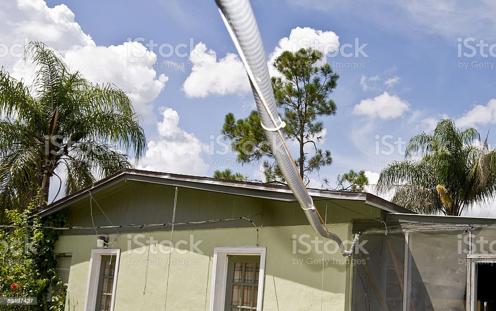 Casa con Power Line Aproaching nell'Area tropicale foto stock royalty-free