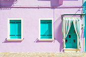 House with purple walls and turquoise windows.
