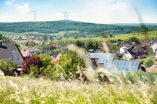 haus mit solarzellen auf dem dach und windturbinen - solarstrom stock-fotos und bilder
