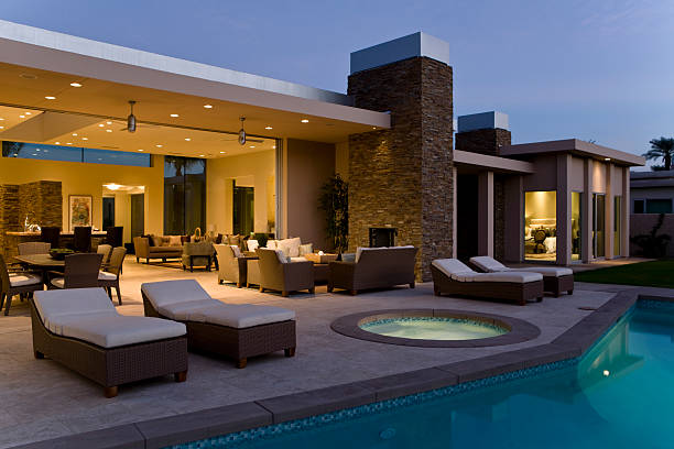 House With Sunloungers On Patio By Pool At Dusk stock photo