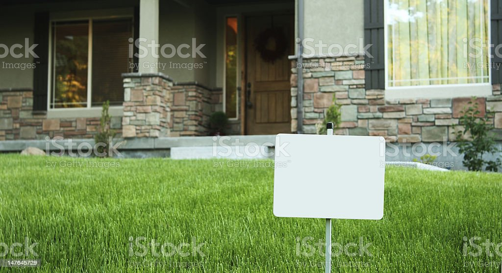 House with yard sign in front stock photo