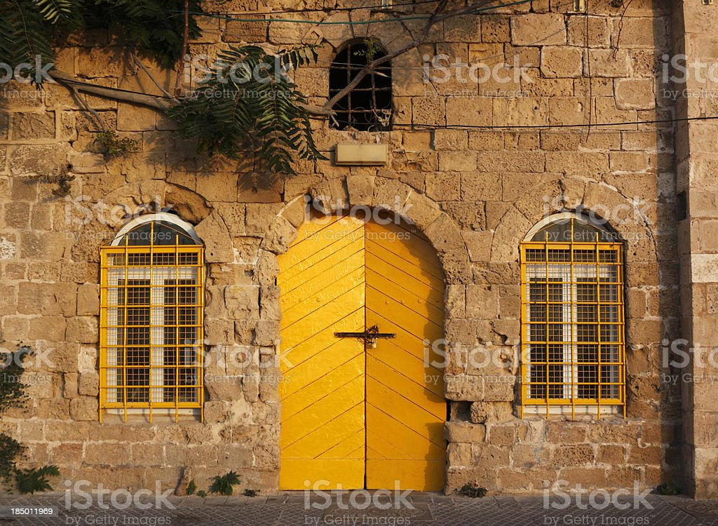 """House with yellow door """"Typical facade of old house with yellow door on the pier in Old Jaffa, Tel Aviv, Israel.More images from Israel:"""" Ancient Stock Photo"""