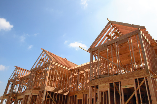 Wooden frame of a new house under construction against a bright sunny sky