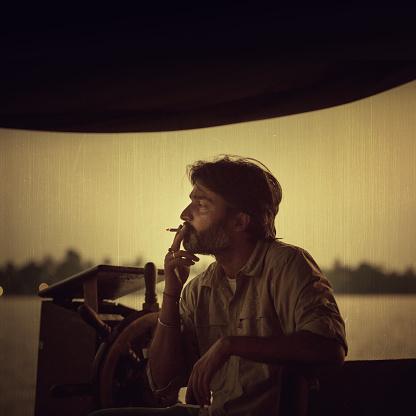 Houseboat capitan smoking a cigaret in Kerala, India