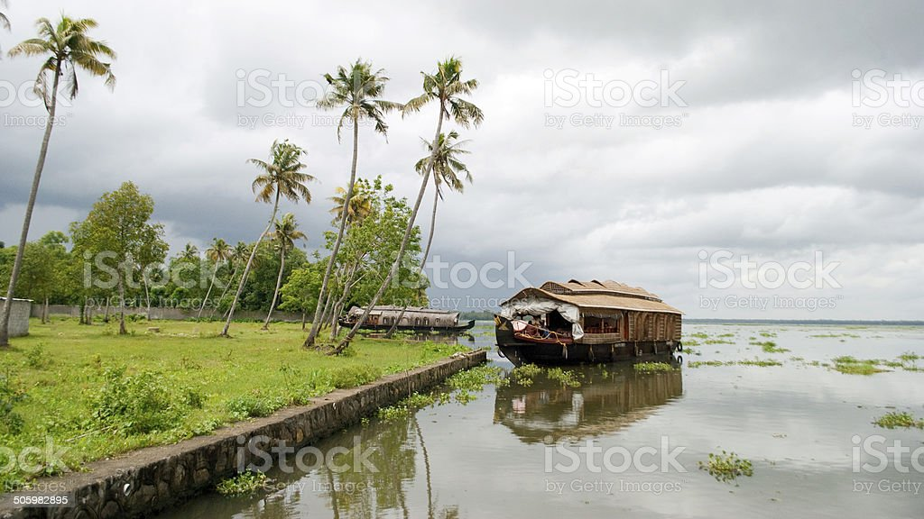 Houseboat in backwaters on a cloudy day Houseboat in Alappuzha, Kerala is a great tourist attraction in India.  A houseboat is seen with a backdrop of dark clouds when it about to rain. Asia Stock Photo