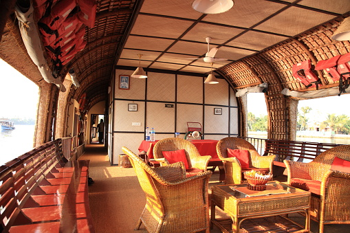 Alleppey Backwaters, Kerala, India - January 24, 2017: A houseboat is comfortably furnished with an open lounge sailing on the Kerala backwaters. The Kerala houseboats in the backwaters are one of the prominent tourist attractions in Kerala. The Kerala Backwaters are a network of interconnected canals, rivers, lakes and inlets.