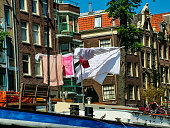 Amsterdam, Netherlands - May 5, 2007: Floating house on a barge in a river channel. The washed clothes are dried on a rope.