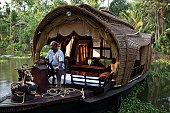 beautiful woman contemplating life from houseboat in Kerala Backwaters - India.