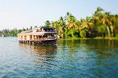 Tilt shift shot of a houseboat on the Kerala Backwaters of Kerala, India.