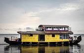 Houseboat yellow image with blue sky and cloud at alleppey kerala india.