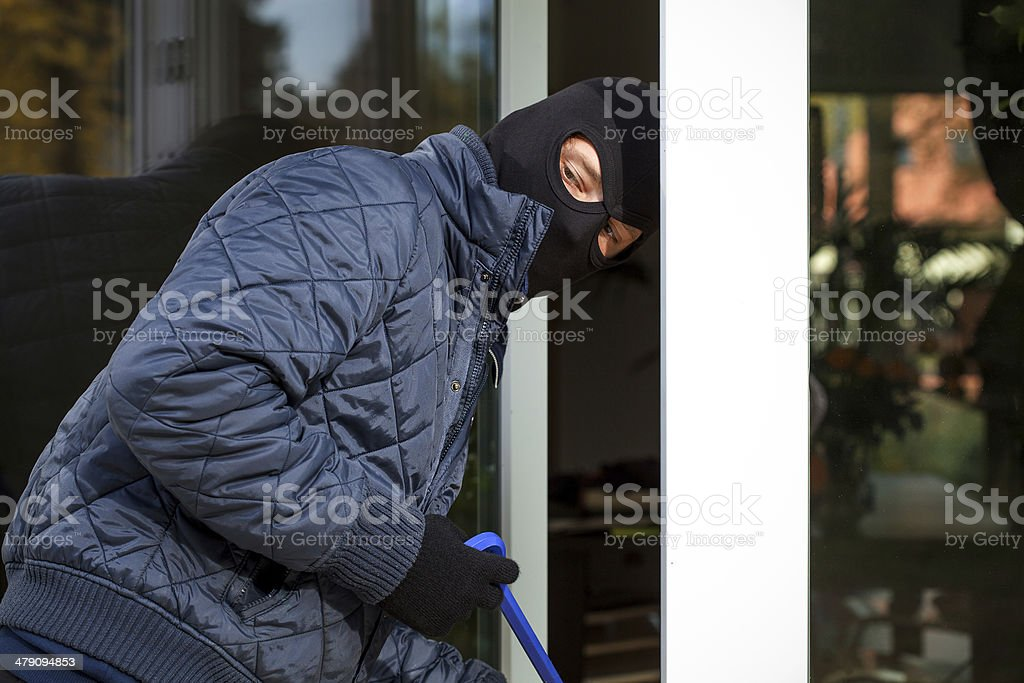 Housebreaker during entering to house stock photo