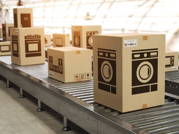 Household appliance in cardboard boxes on conveyor roller in distribution warehouse E-commerce,  delivery and packaging service concept. stock photo