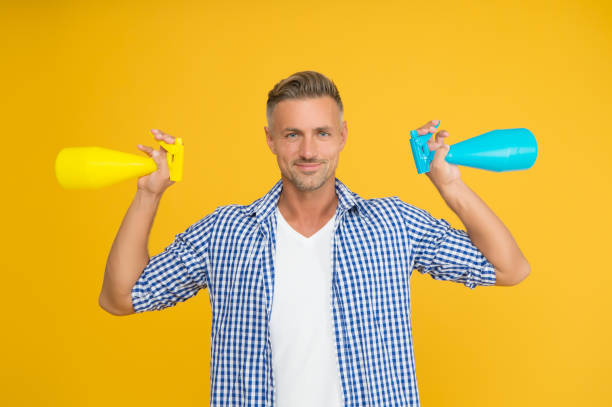 Household cleaning products kill coronavirus. Happy guy hold spray bottles. Using household cleaners and disinfectants. Household hygiene. Routine cleaning and disinfection of household stock photo