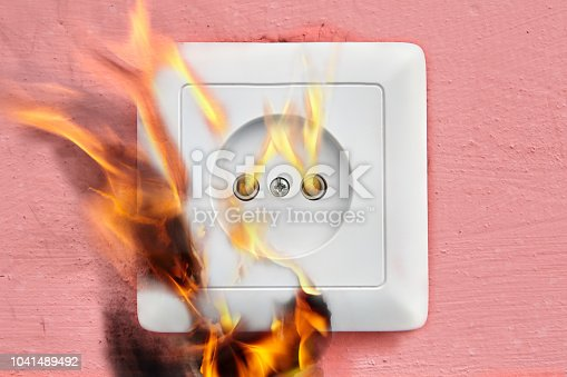 istock Household fire due to faulty wiring, electrical socket flames. 1041489492