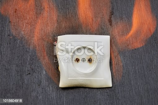 istock Household fire, Ignition of the plastic wall socket. 1015604918