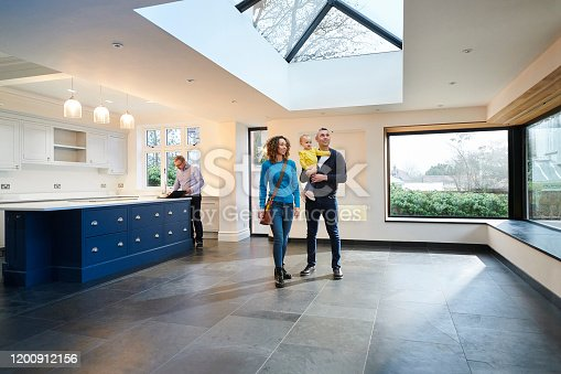 young family looking round new house with estate agent