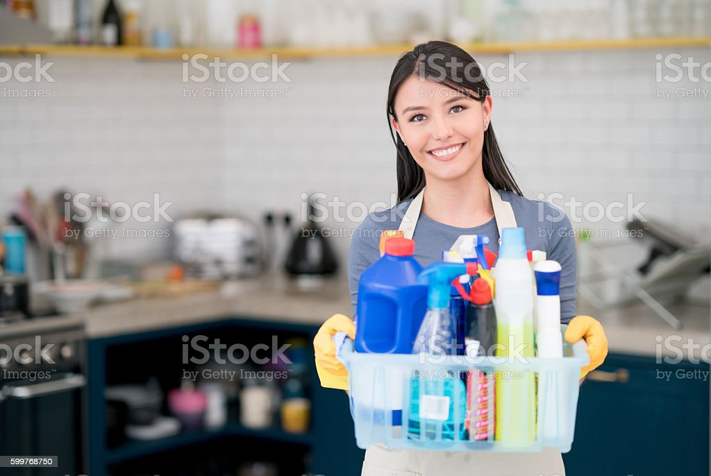 Housekeeper holding cleaning products stock photo