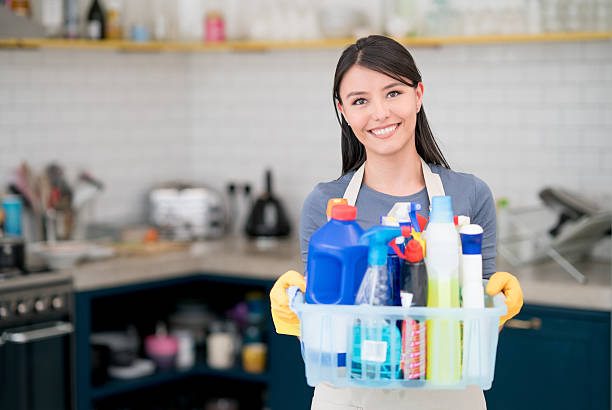 Housekeeper holding cleaning products Portrait of a housekeeper holding cleaning products while working at home and looking at the camera smiling cleaning equipment stock pictures, royalty-free photos & images