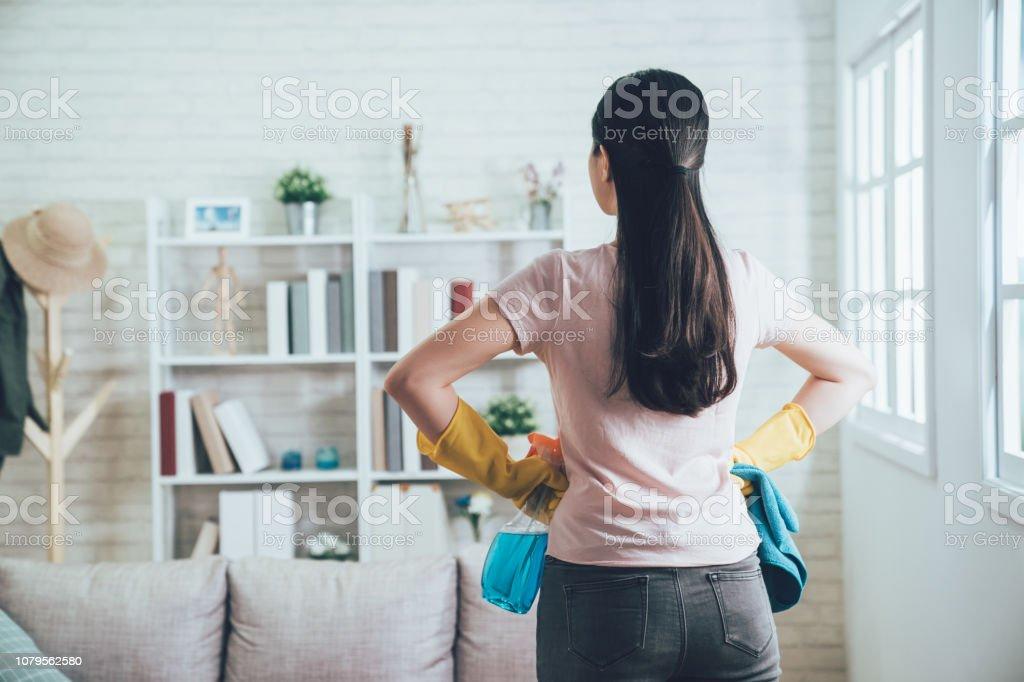 huishoudster te kijken naar de schone woonkamer - Royalty-free Afwashandschoen Stockfoto