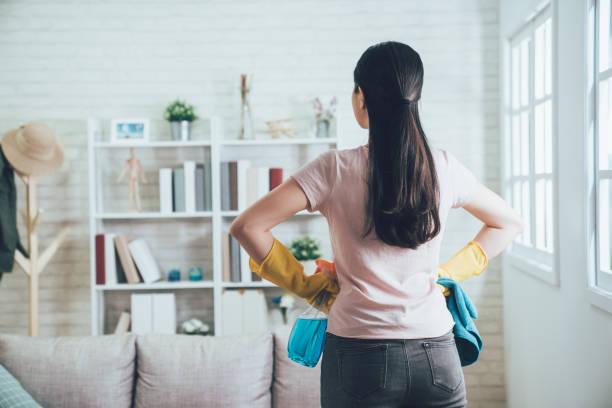 huishoudster te kijken naar de schone woonkamer - opruimen stockfoto's en -beelden