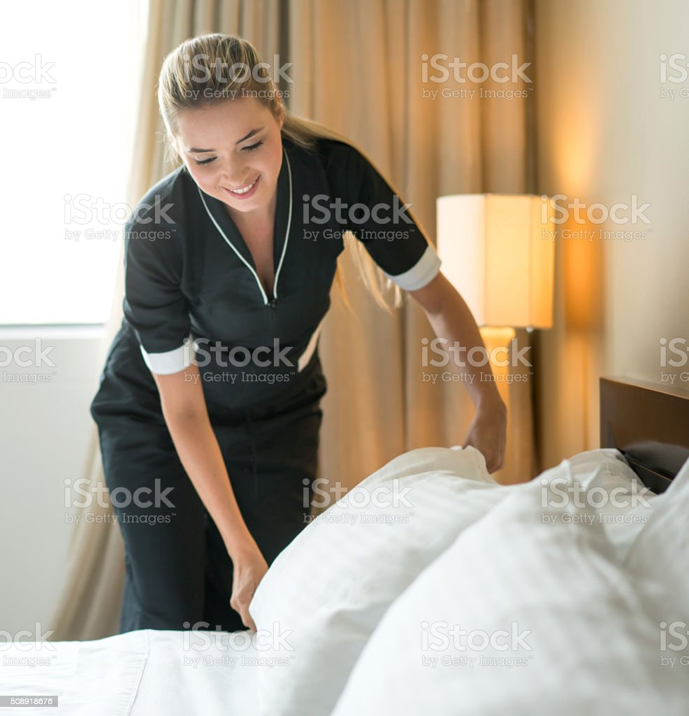 Housekeeper making the bed at a hotel stock photo